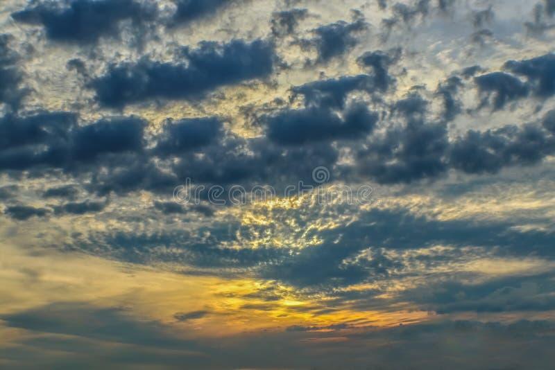 Lumière jaune se renversant par les nuages gonflés foncés au coucher du soleil - fond de ciel photographie stock