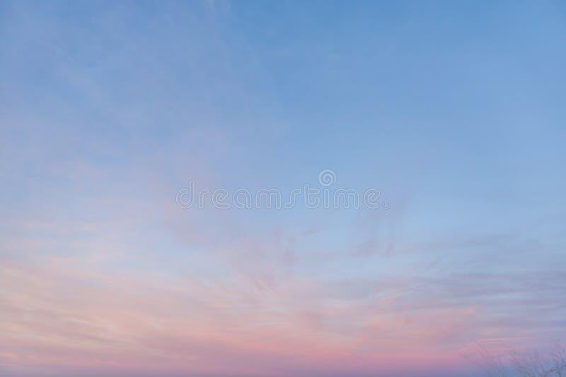 Lumière partiellement nuageuse de crépuscule de rose en pastel et de pourpre avec le ciel bleu photos stock