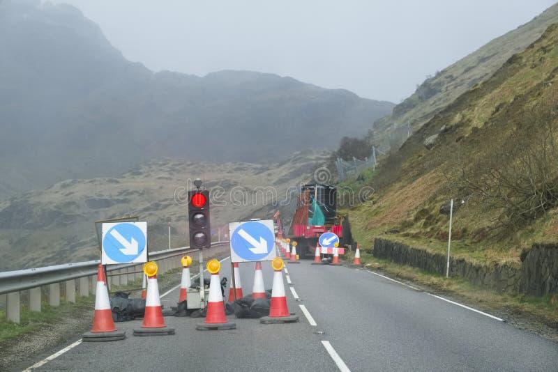 Lumière rouge aux courses sur route et aux cônes du trafic avec le signe de sécurité à la scène d'isolement rurale de montagne photographie stock
