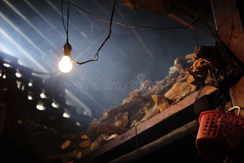 Lumière solitaire sur le magasin rustique de bois de chauffage photo stock
