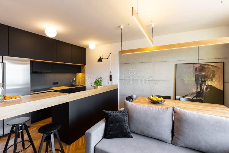 Lumières au-dessus de partie supérieure du comptoir dans l'intérieur noir ouvert de cuisine avec le gris photos libres de droits