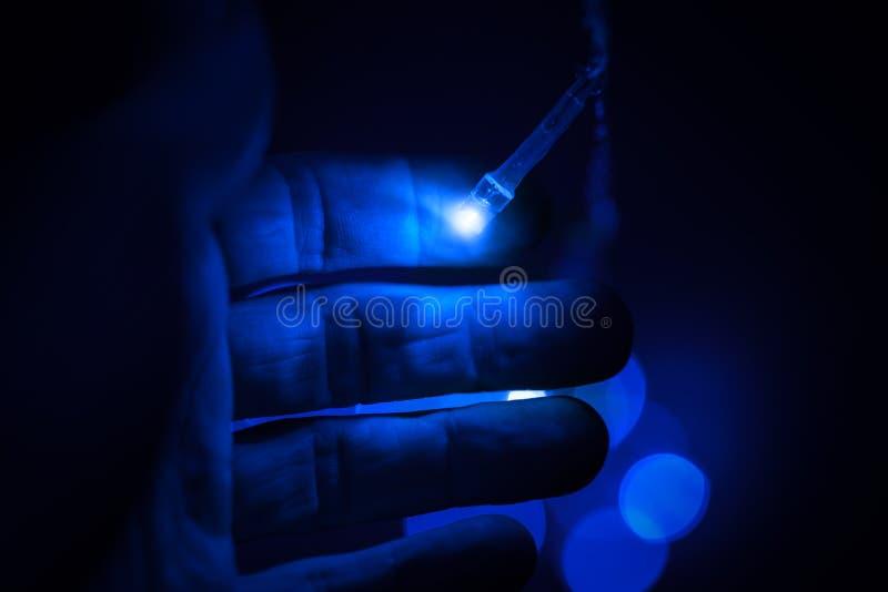 Lumières bleues de DEL et main mâle photo stock