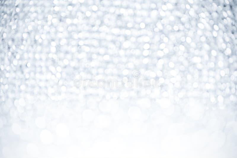 Lumières brouillées brillantes de lumières blanches de résumé de glister de bokeh de fond de concept de l'espace argenté de copie photographie stock libre de droits