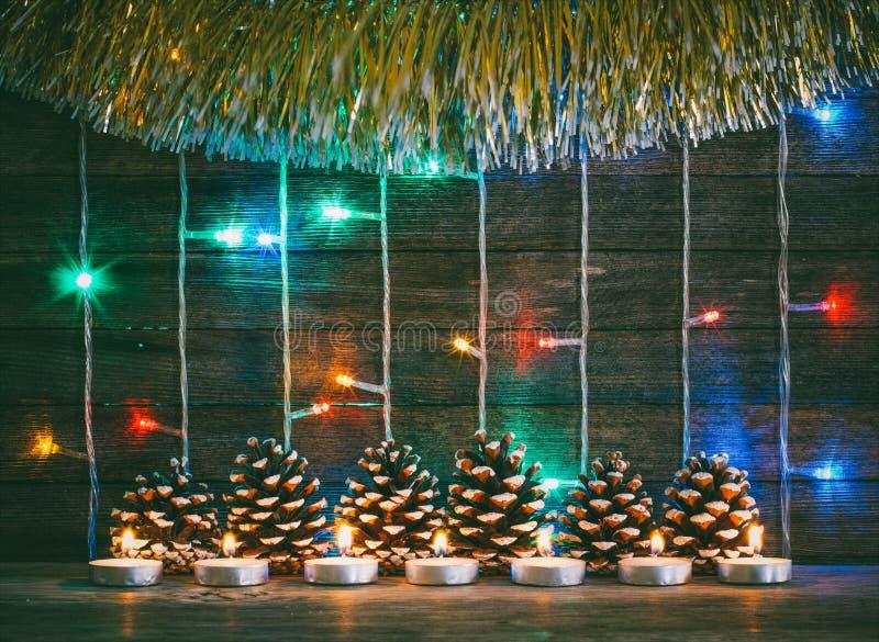 Lumières colorées des guirlandes, des cônes de sapin et des bougies sur le fond de vieux panneaux de grange image libre de droits