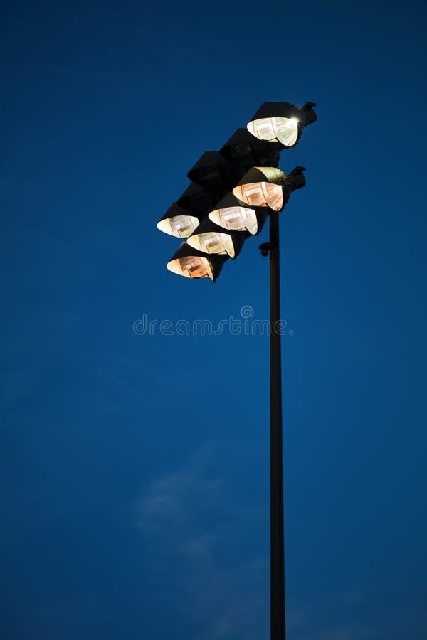 Lumières d'inondation de stade sur le fond déprimé coloré de ciel photos libres de droits