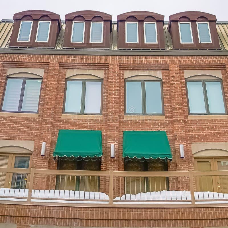 Lumières de ciel nuageux et de ficelle de place au-dessus d'un bâtiment avec le mur de briques et le balcon neigeux photos libres de droits