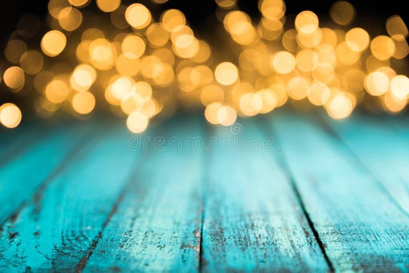 lumières de fête de bokeh sur la surface en bois bleue, photos stock