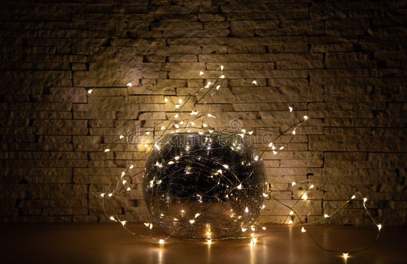 Lumières de guirlande autour de vase à miroir en verre sur le fond en pierre beige Dans l'obscurité photo stock