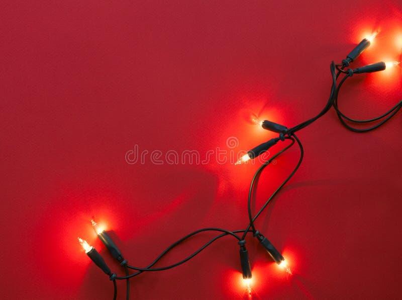 Lumières de guirlande de Noël sur le fond de papier rouge Vue supérieure images libres de droits