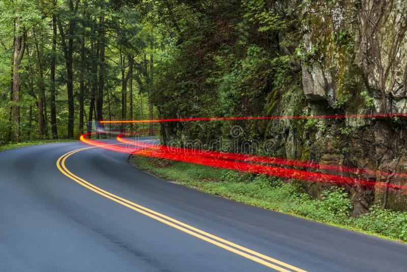 Lumières de queue d'automobile striant autour de la courbe fumeuse de montagne photo libre de droits