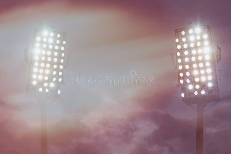 Lumières de stade contre le ciel de nuit foncé images stock