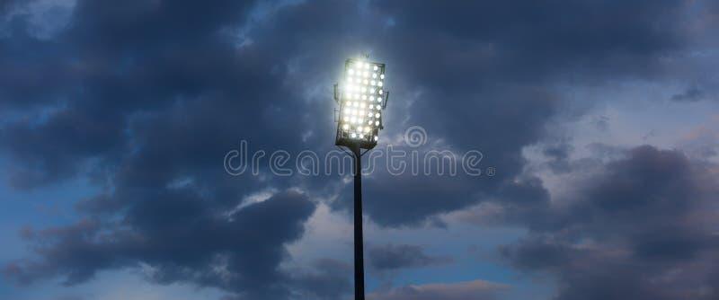 Lumières de stade contre le ciel de nuit foncé photographie stock