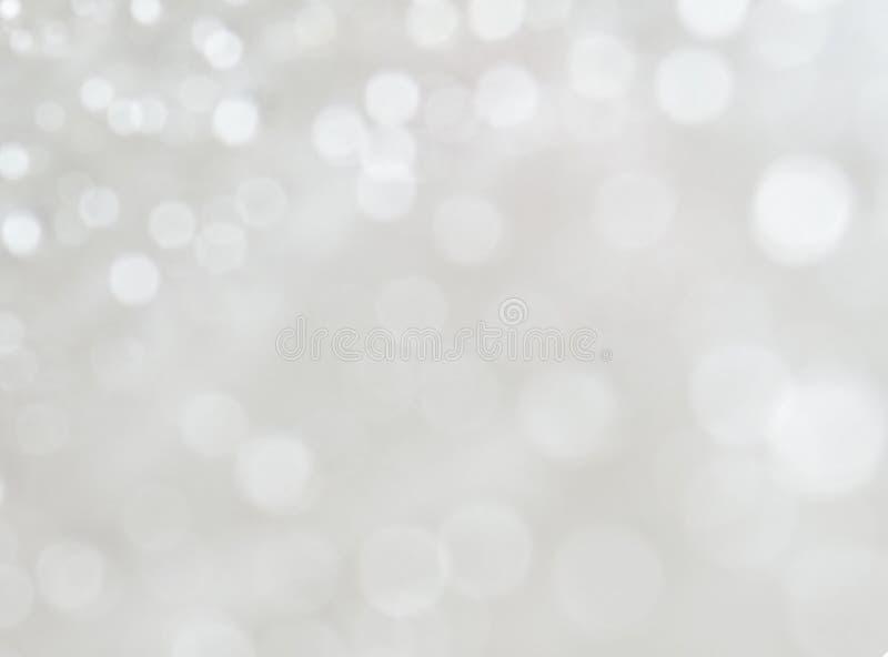 Lumières defocused de bokeh blanc sur le fond argenté photographie stock