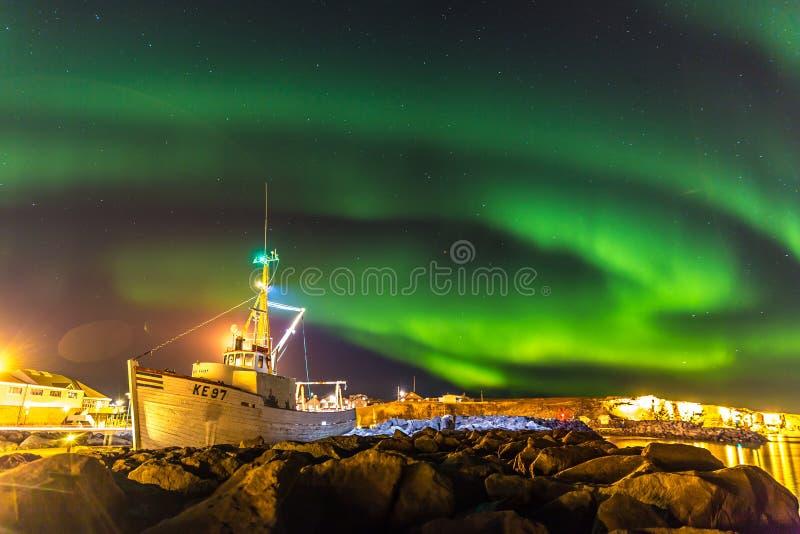 Lumières du nord étonnantes à l'Islande, au bateau et aux roches dans le premier plan images libres de droits