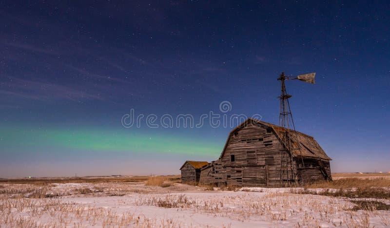 Lumières du nord au-dessus de grange, de poubelles et de moulin à vent de cru en Saskatchewan image stock
