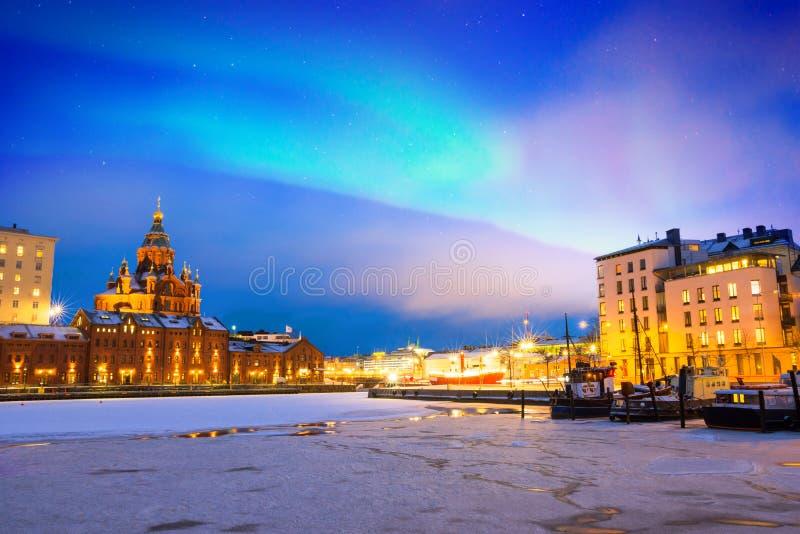 Lumières du nord au-dessus du vieux port congelé dans le secteur de Katajanokka avec la cathédrale orthodoxe d'Uspenski à Helsink photo stock