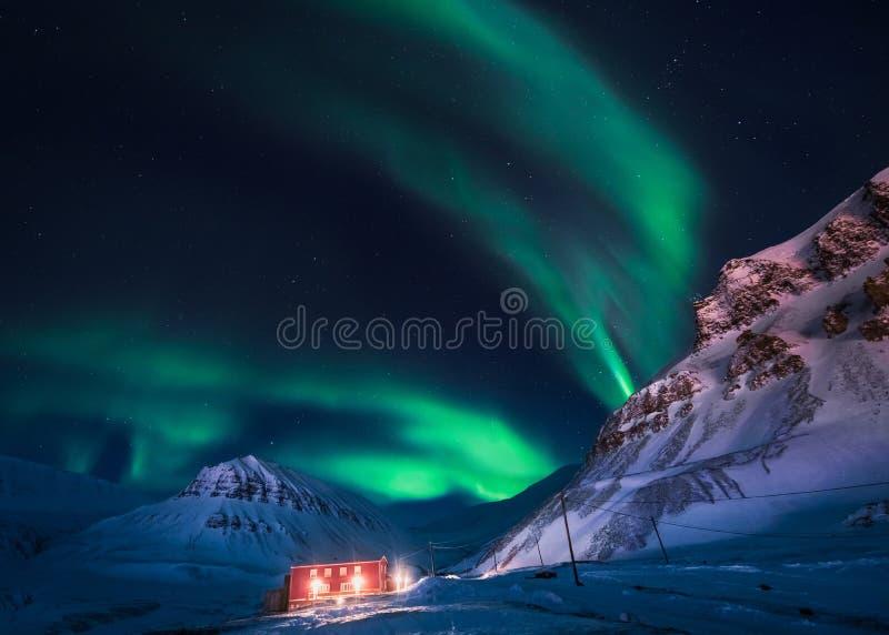 Lumières du nord dans la maison de montagnes du Svalbard, ville de Longyearbyen, le Spitzberg, papier peint de la Norvège photo libre de droits