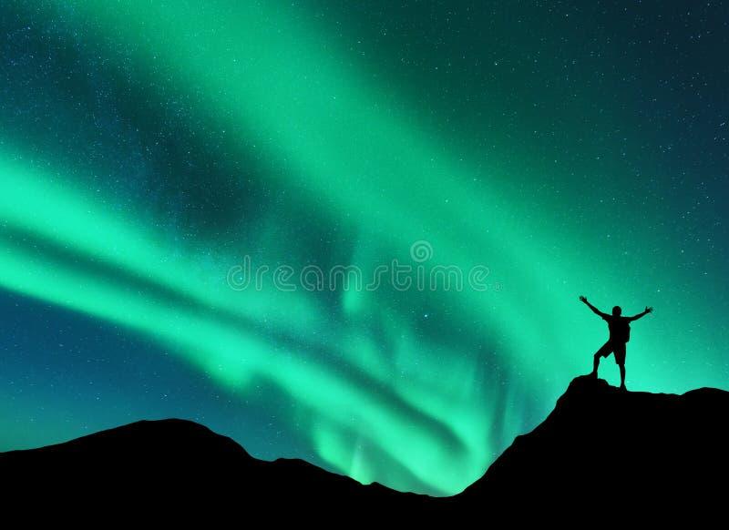 Lumières du nord et silhouette de tenir l'homme heureux l'aurore photo libre de droits