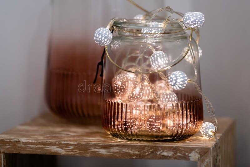 Lumi?res f?eriques blanches et roses de th? dans le pot en verre color? avec le fond brouill? image stock