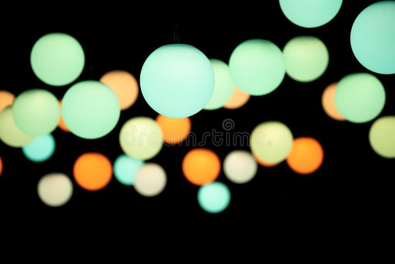 Lumières pendantes colorées sur un fond foncé illustration stock