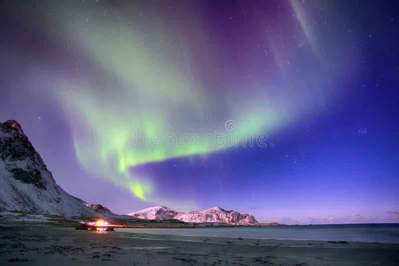Lumières polaires dans le ciel au-dessus des montagnes sur la plage du nord en Norvège photo stock