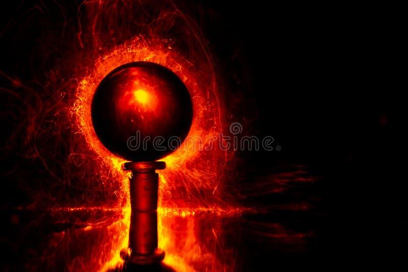 Lumières rouges sous forme de fibres lumineuses minuscules derrière une sphère transparente image libre de droits