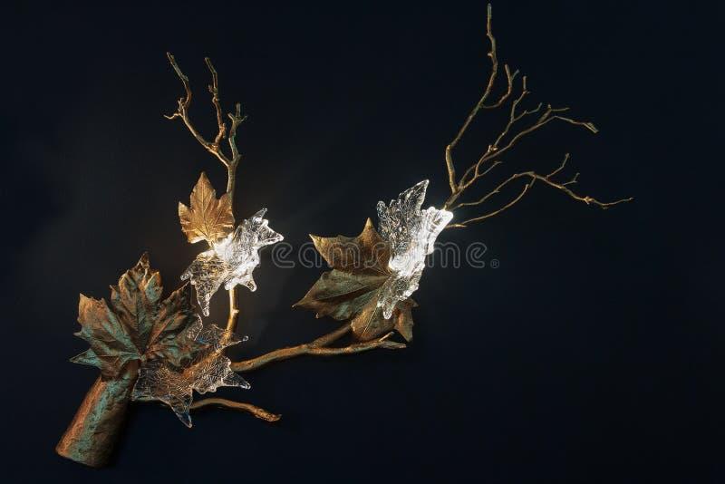 Luminaire luxuoso sob a forma das folhas e das flores na parede fotografia de stock royalty free
