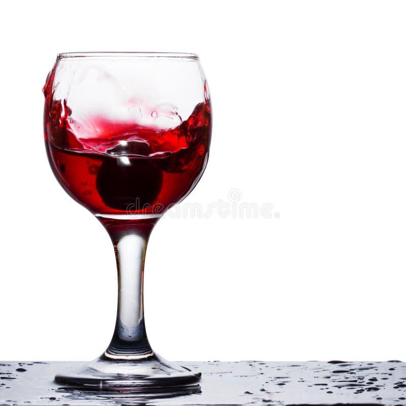 Luminoso spruzza di vino rosso su entrambi i bordi del vetro immagini stock