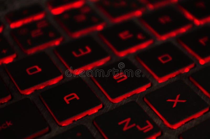 Luminoso vermelho, backlit no portátil ou no computador do keyborad do jogo na obscuridade Teclado do portátil do computador com  imagem de stock
