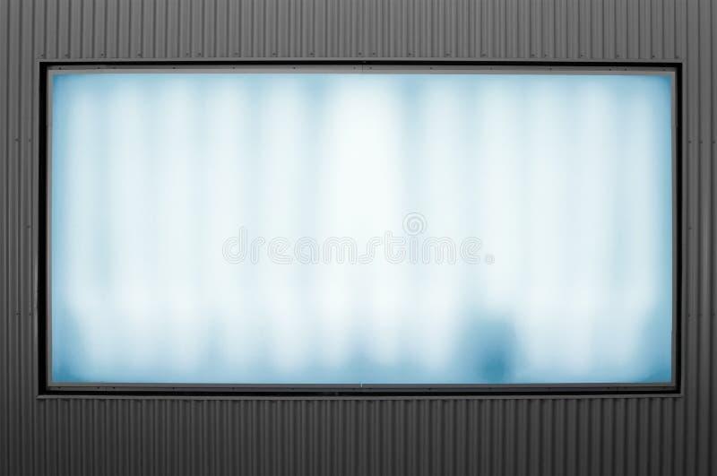 Luminous advertising billboard on metal wall stock image