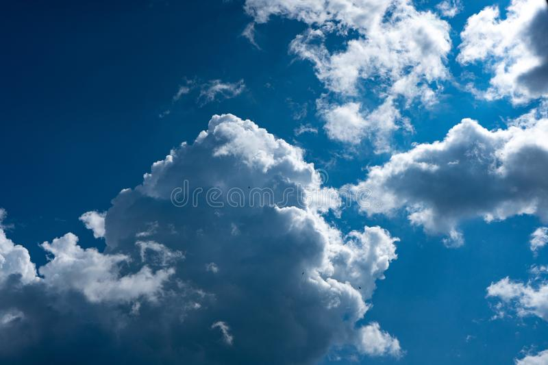 Luminous clouds set against a dark blue sky in the sun. Wonderful blue glowing cloud stock photography
