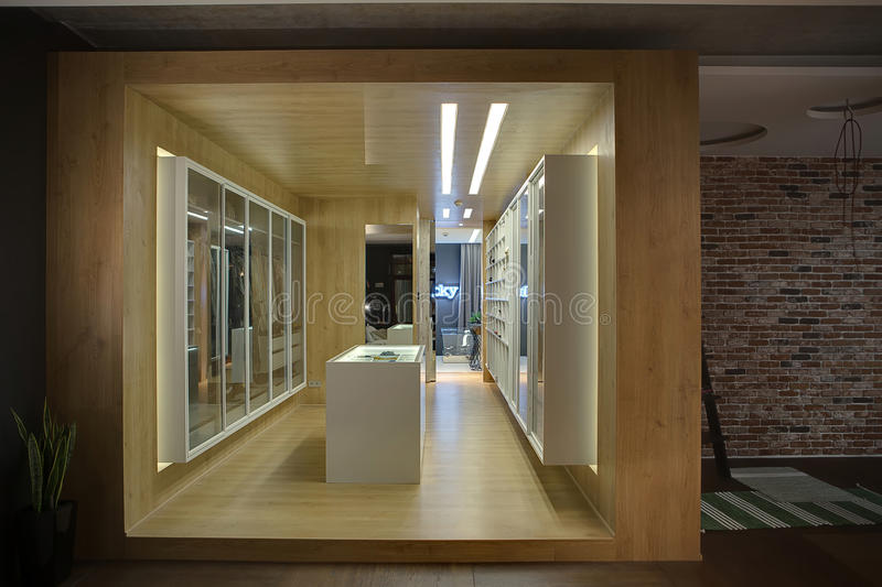 Luminous dressing room. Stylish wooden walk-in closet with white wardrobes, shelves, stand and mirrors. There are luminous lamps. On the right side there is a royalty free stock photo