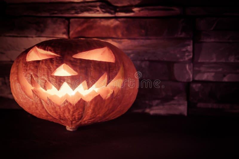 Luminous halloween Jack O' lantern in dark on stone background stock photography