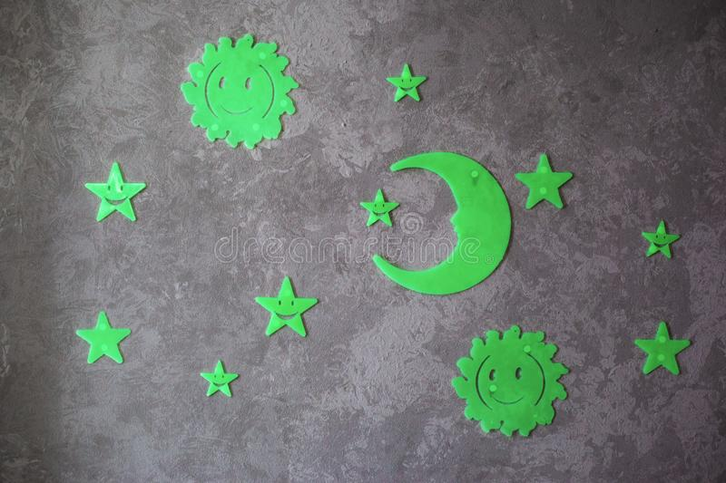 Luminous phosphoric sun, moon and stars on a gray background. Close-up royalty free stock photos