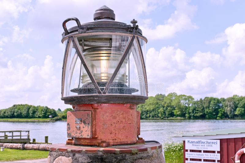 Luminous ship`s lantern on the canal at the height of the fish restaurant Aalkate near royalty free stock photography