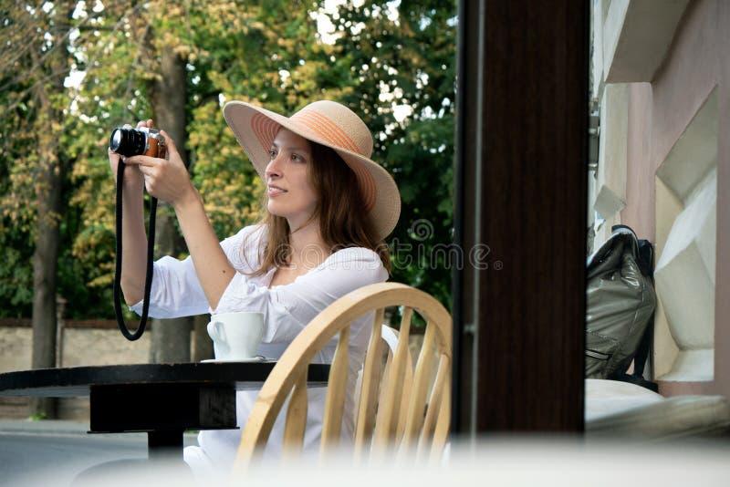Lumix blanc de tir de panasonic de café de tasse de femme d'appareil photo numérique de rue de café de terrasse de fille de chape image stock