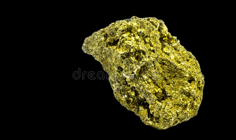Lump of shiny cat gold, pyrite, which looks similar to real gold, isolated against a black background.  stock photo