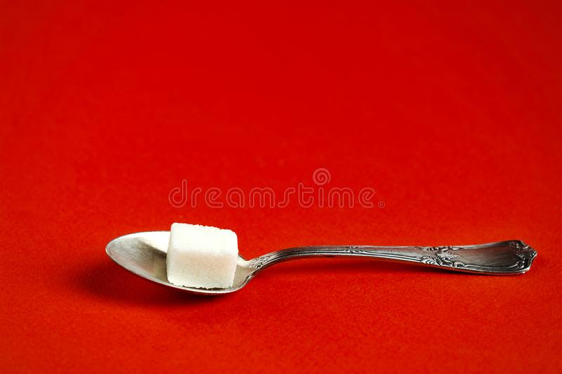 Lump sugar in an aluminum spoon. On a red background - vintage style stock photo