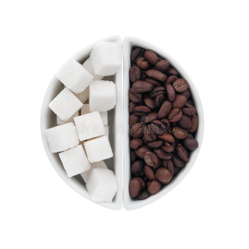 Lump sugar and coffee beans in a ceramic bowl stock image