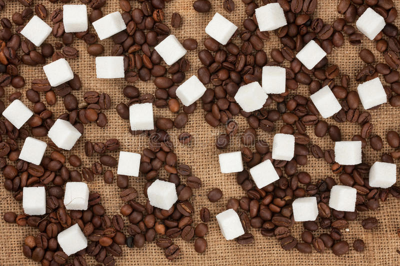 Lump sugar and coffee beans on sackcloth royalty free stock image