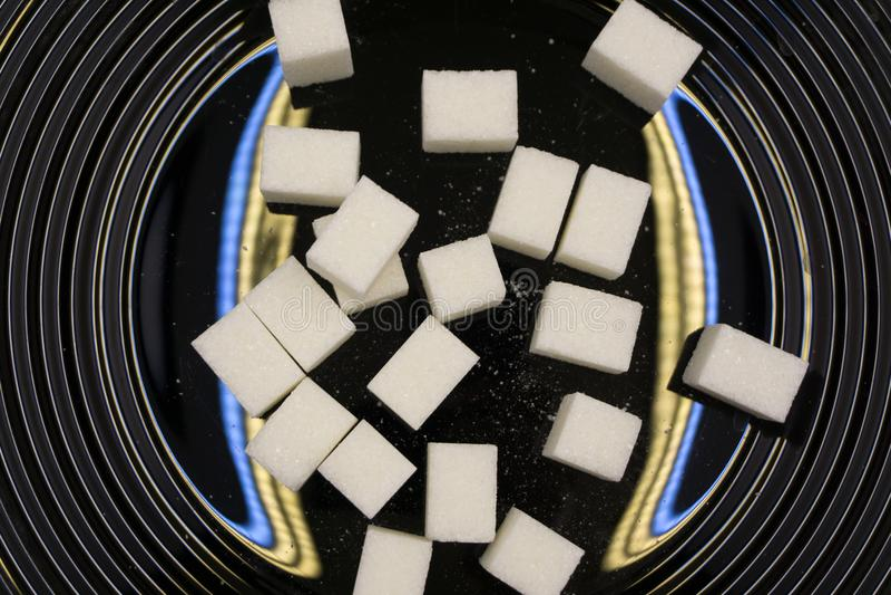 Lump sugar cube on black background . royalty free stock photos