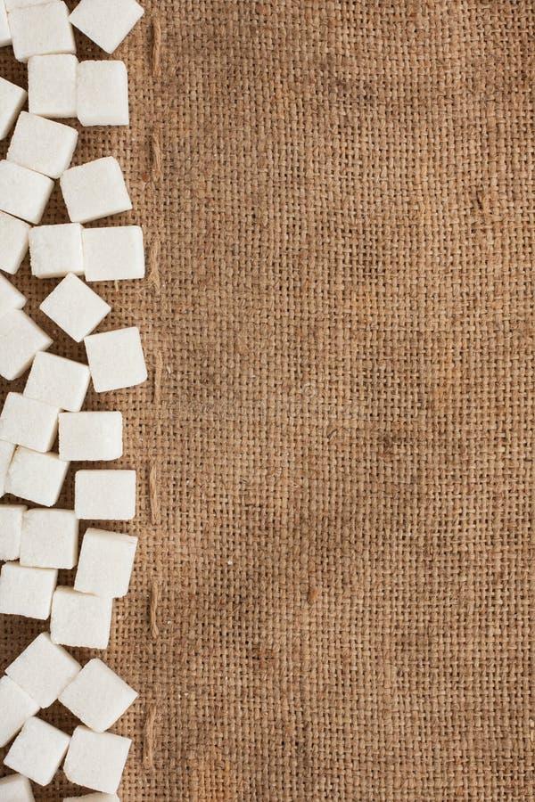 Lump sugar lying on burlap royalty free stock image