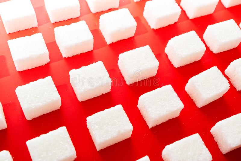 Lump sugar on red background. Lump sugar on a red background perspective rows royalty free stock image
