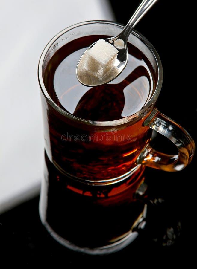 Lump sugar in tea stock photography