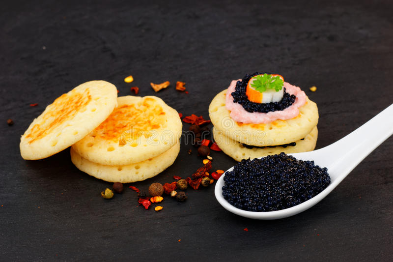 Lumpfish caviar and Homemade pancake canape. On slate stone plate for finger food party royalty free stock photo