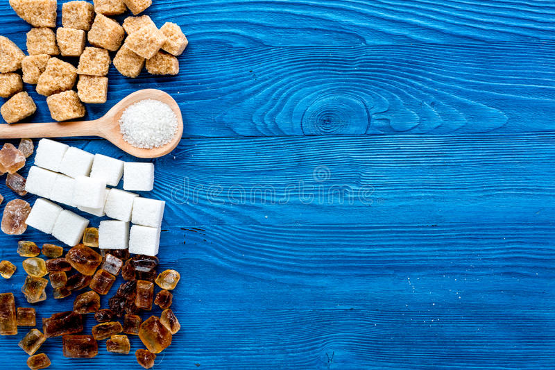 Lumps and sanding sugar for sweets on blue kitchen table background top view mock up. Lumps and sanding sugar for cooking sweets on blue kitchen table background royalty free stock photo