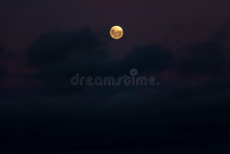 Luna anaranjada con las nubes crepusculares púrpuras fotos de archivo