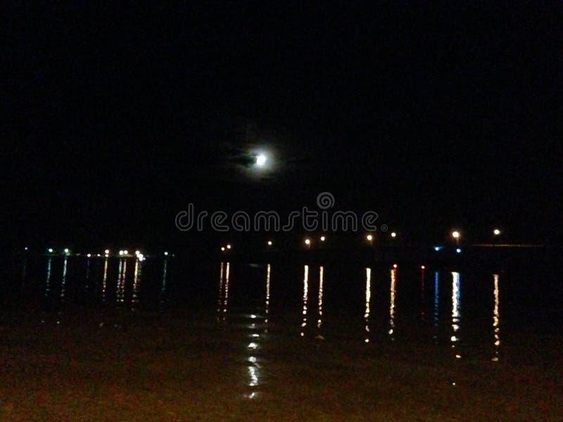Luna che alza fuori da dietro le nuvole che riflettono sopra l'acqua fotografia stock