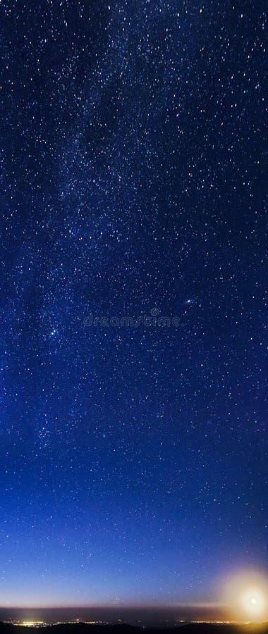 Luna che aumenta sopra le montagne e le luci della città fotografie stock