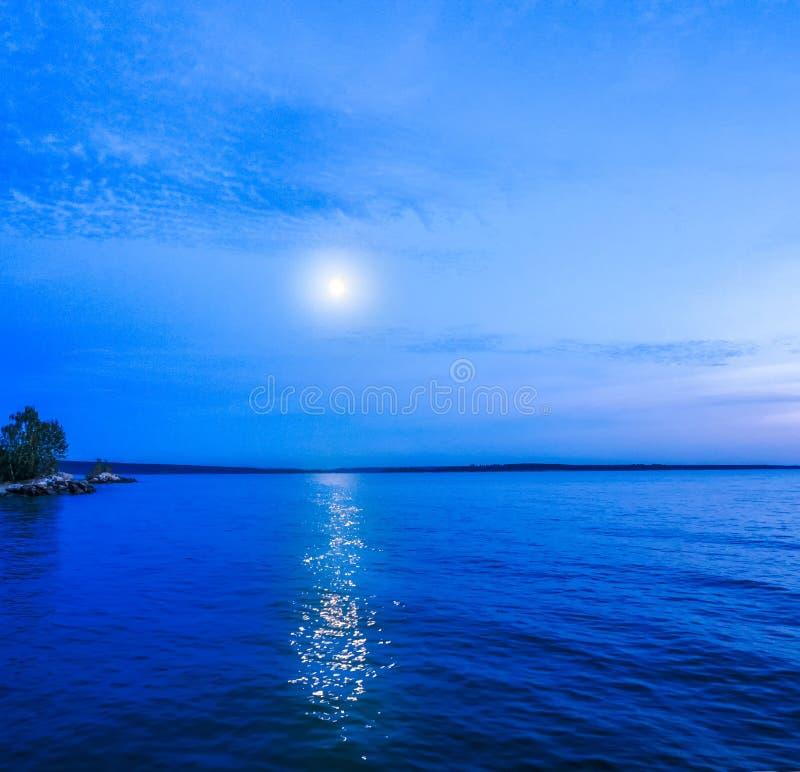 Luna in cielo notturno sopra l'acqua di mare illuminata dalla luna Priorità bassa di corsa fotografia stock